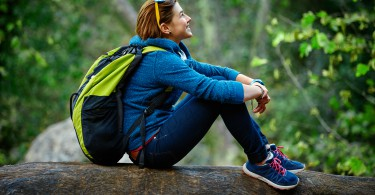 Active healthy woman hiking in beautiful forest. Portrait of happy smiling young woman resting of forest clearing during hike holidays.