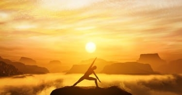 Woman standing in side angle yoga position, meditating on the top of a mountain above clouds at sunset. Zen, meditation, peace