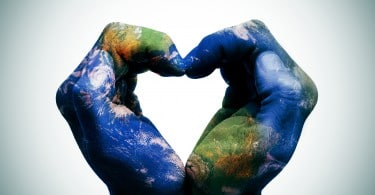 a world map in man hands forming a heart (Earth map furnished by NASA)