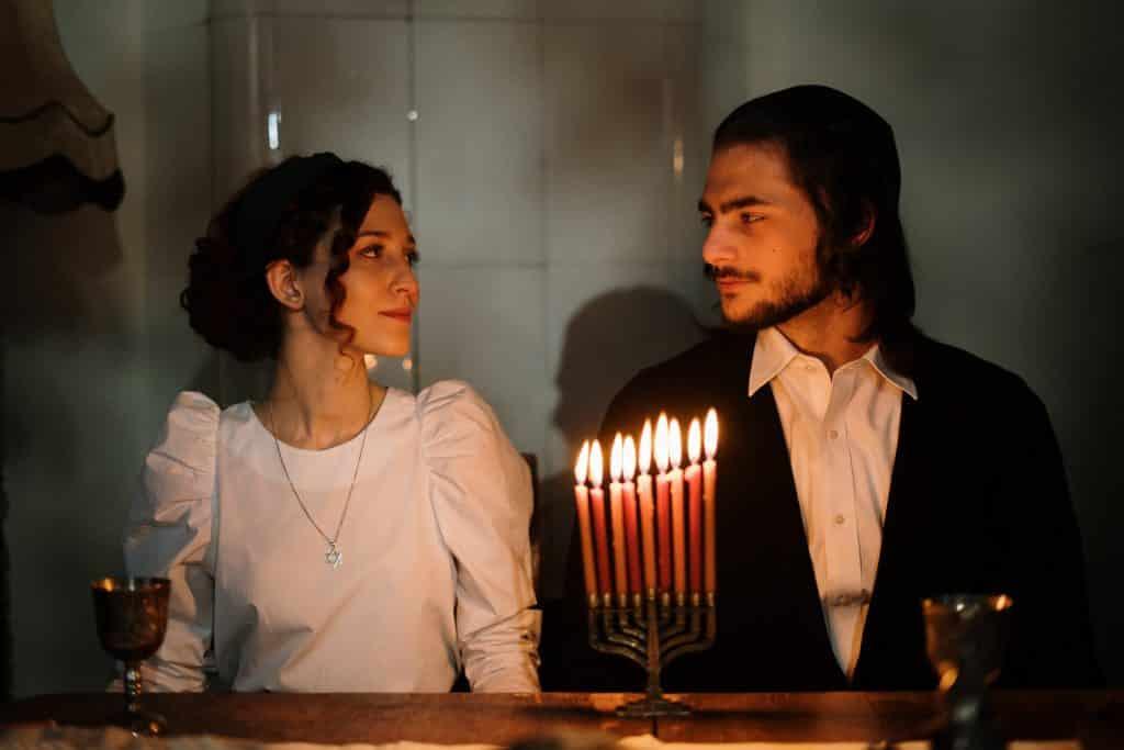 Casal de judeus sentados à luz de velas.
