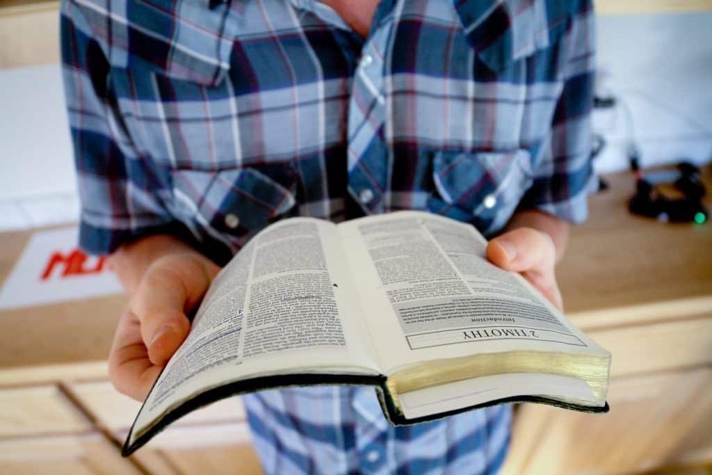 Pessoa em pé lendo uma Bíblia.