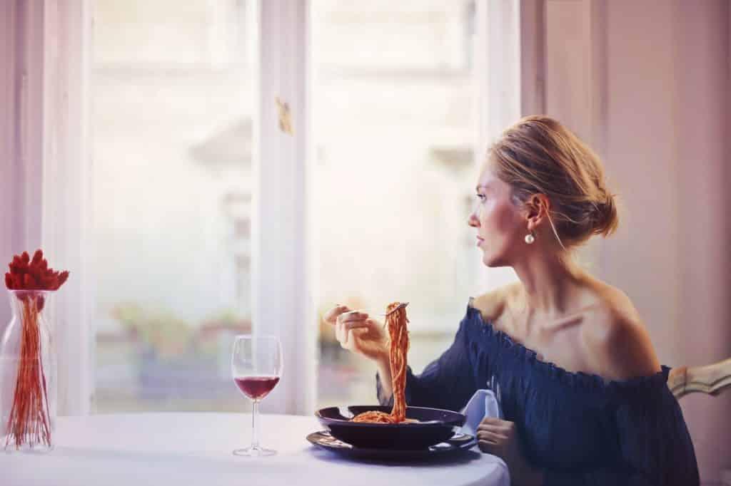 Mulher comendo macarrão e bebendo uma taça de vinho enquanto olha pela janela.