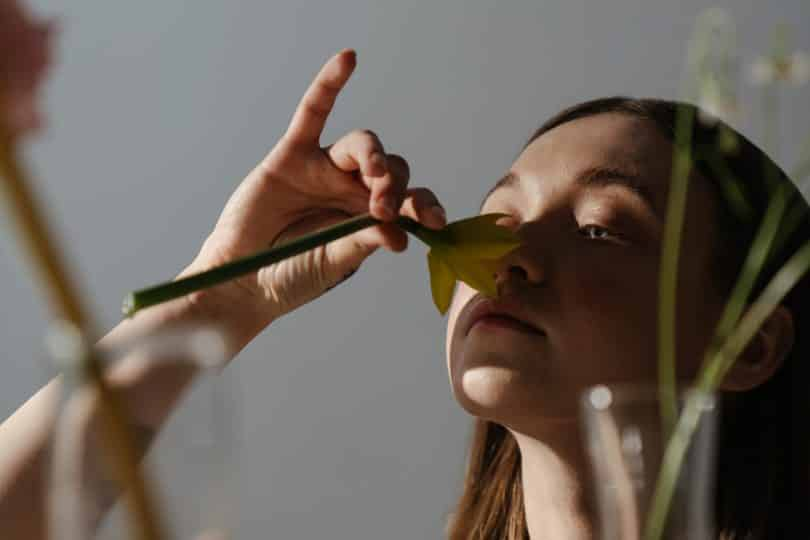 Mulher cheirando flor olhando para frente