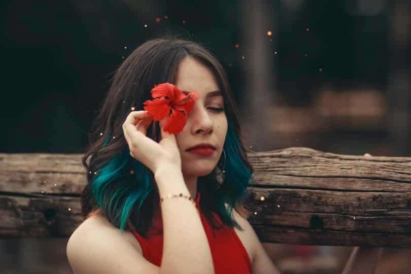 Mulher de olhos fechados segurando uma flor na direção dos olhos