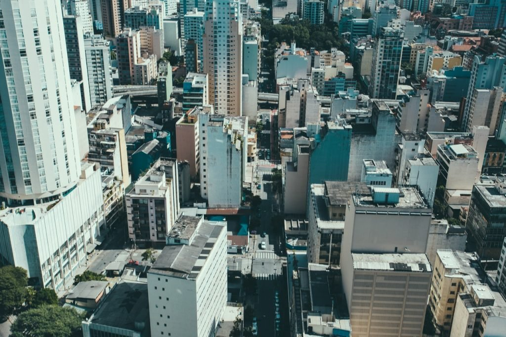 Imagem de uma cidade repleta de prédios vista de cima, durante o dia.