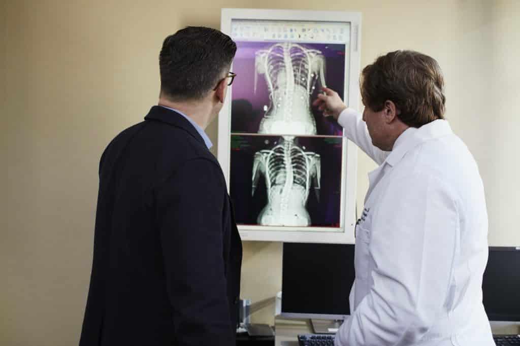 Médico e paciente examinando resultados de exames raio X.