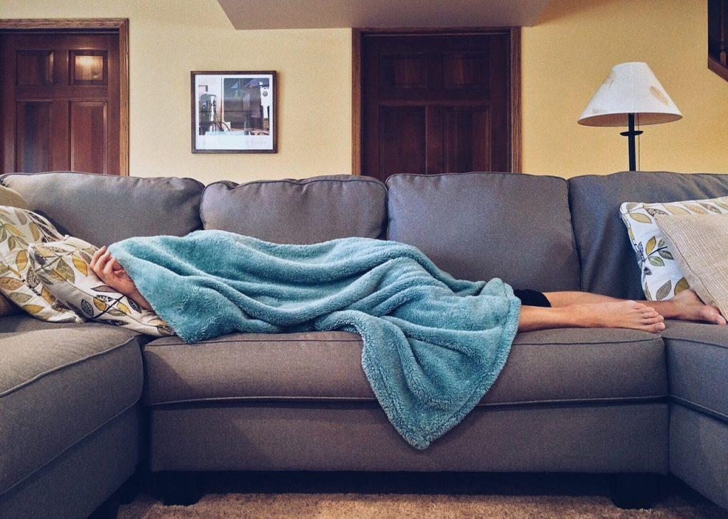 Pessoa deitada no sofá sob uma coberta.
