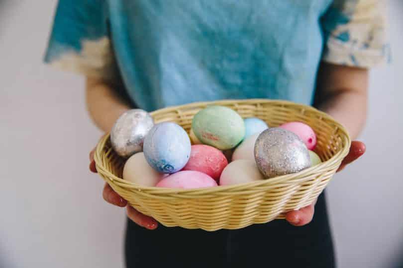 Mulher segurando cestas com ovos coloridos