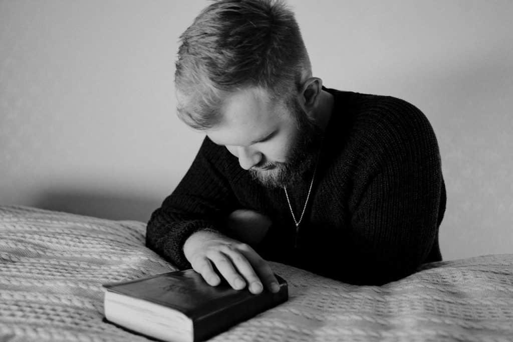 Imagem em preto e branco de um homem segurando uma bíblia enquanto reza.