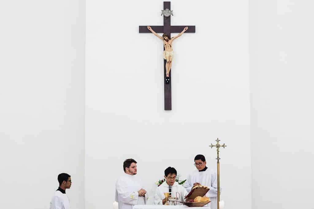 Padre conduzindo uma missa católica em uma igreja.