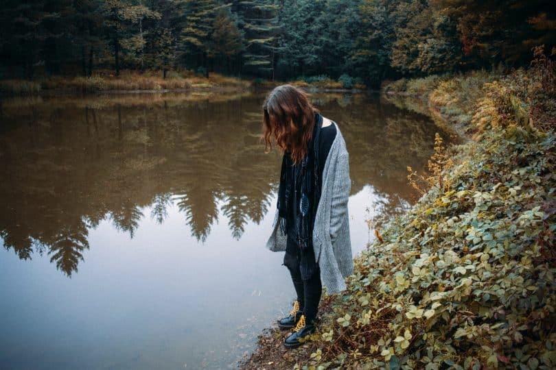 Mulher ao lado de um lago olhando para baixo