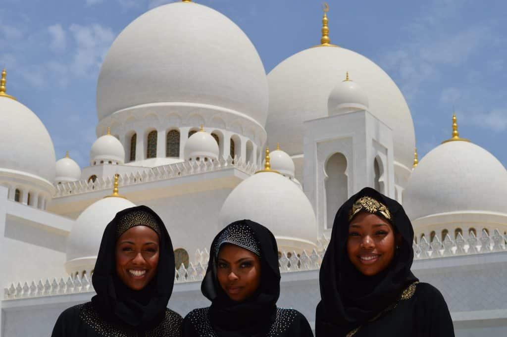 Três jovens muçulmanas em frente a uma mesquita.