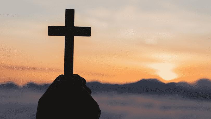 Silhueta de mãos segurando uma cruz durante o pôr do sol