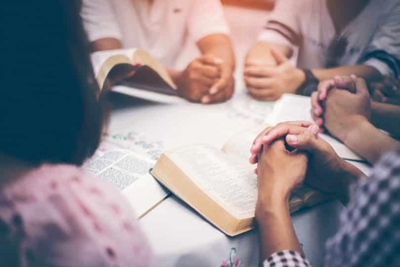 Pessoas lendo a bíblia em uma mesa