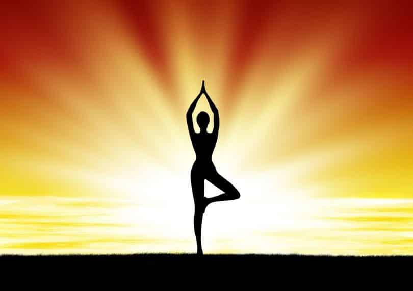 Silhueta de mulher praticando yoga no pôr do sol em praia.