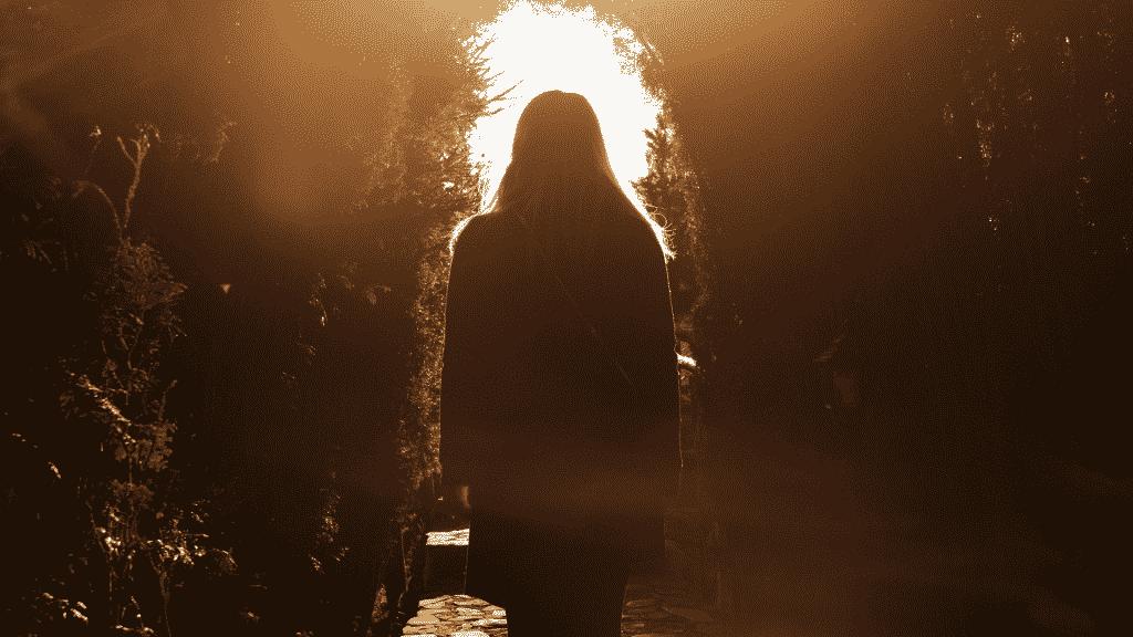 Silhueta de mulher caminhando pelo bosque até a luz