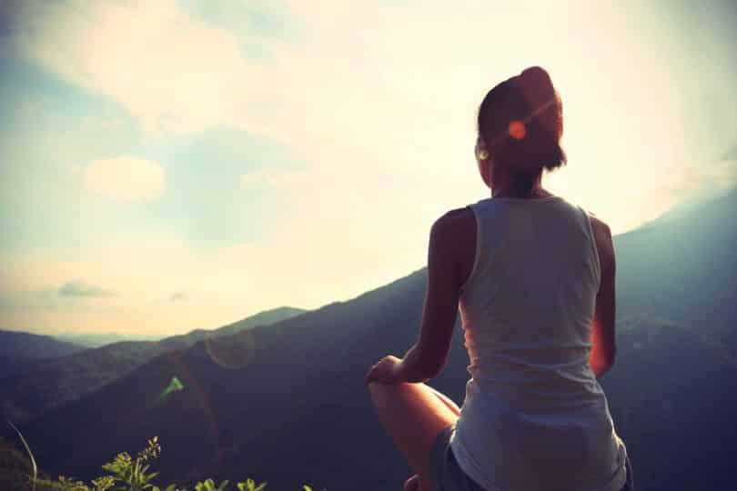 Mulher sentada em uma montanha em direção ao sol