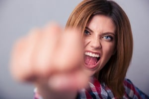 Angry woman hitting with fist on camera and shouting over gray b