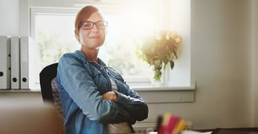 Confident Young Office Woman Sitting at her Desk with Arms Crossing Over her Stomach Smiling at the Camera Against the Glass Window of the Office.