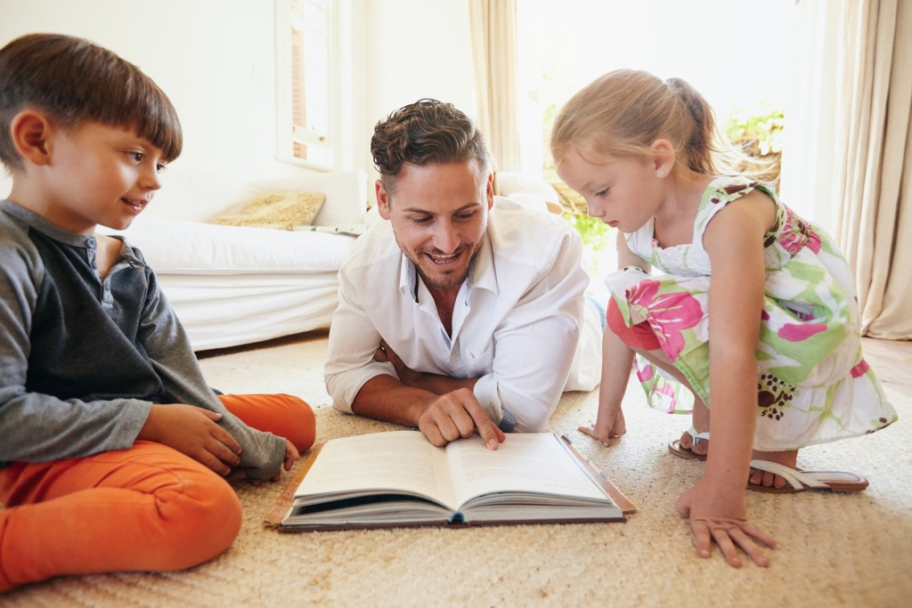 Family reading a book on the floor in the living room. Father reading stories to his son and daughter at home. Young man little boy and little girl reading story book.