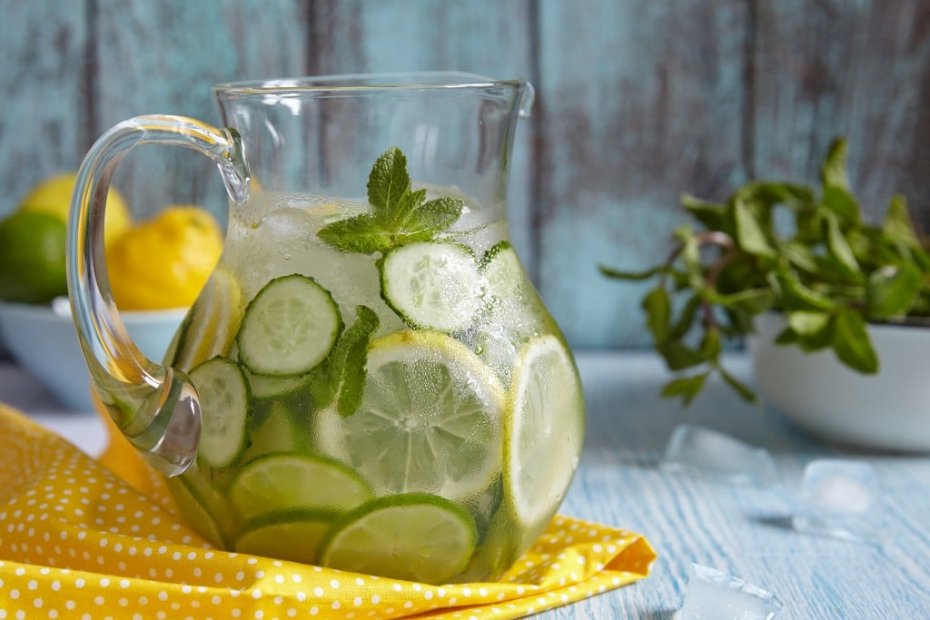 Fruit water with lemon, lime, cucumber and mint in glass pitcher ** Note: Shallow depth of field