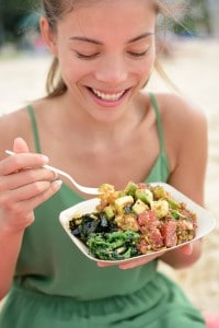 Woman eating local Hawaii food dish Poke bowl salad. Girl enjoyi
