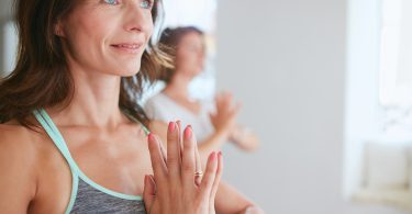 Close up shot of happy mature woman doing yoga looking away smiling. Women in yoga pose vrikshasana using Namaste.