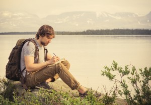 Young Man Traveler with backpack reading book and writing notes