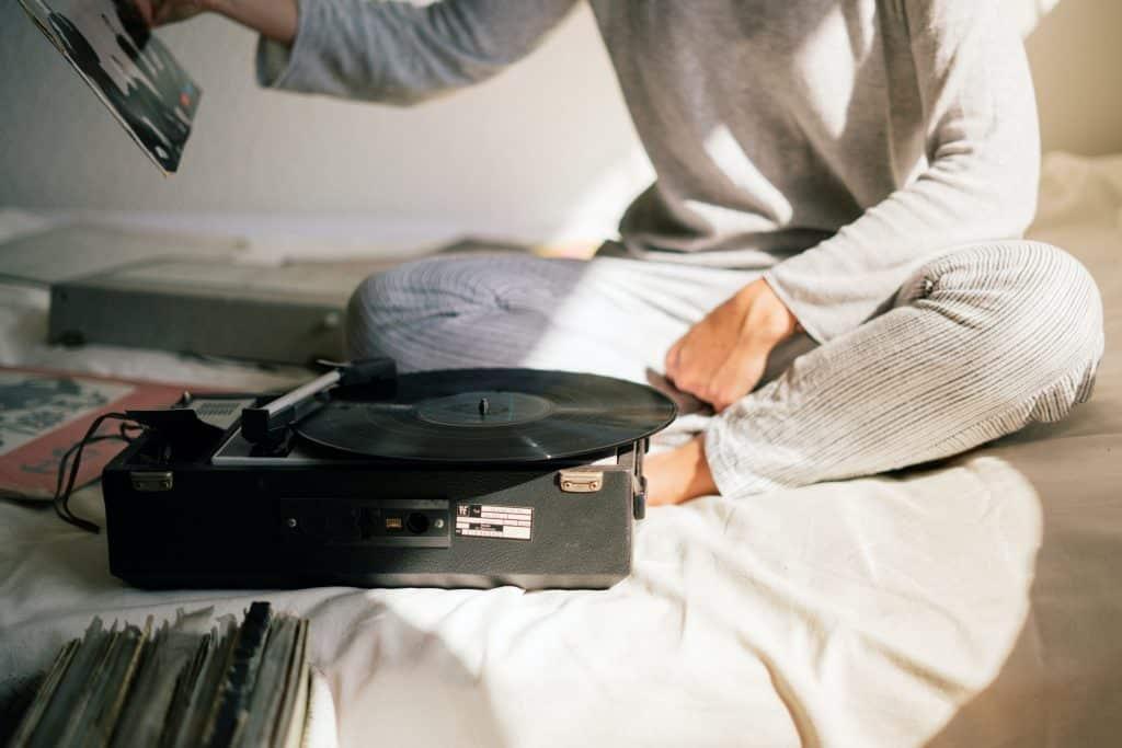 Mulher sentada na cama com discos de vinil e uma vitrola