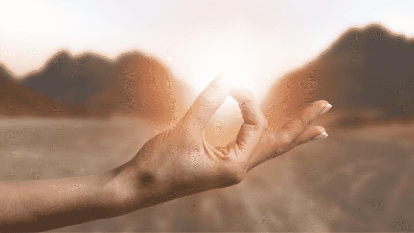 Mão de pessoa meditando durante por do sol