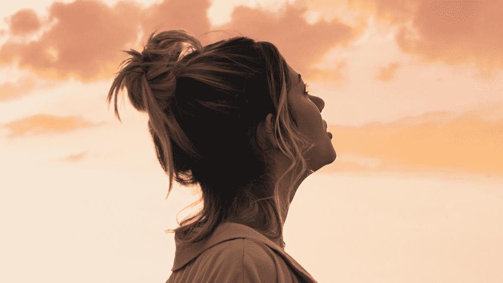 Mulher olhando pensativa para o céu durante o por do sol