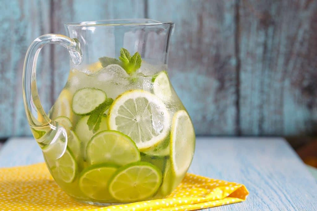 Água com fatias limão e lima em uma jarra, sobre um pano amarelo em uma mesa branca.