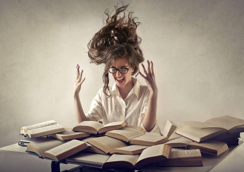 Mulher com cabelos elevados. Suas mãos estão erguidas e ela está sentada à mesa com diversos livros abertos sobre a superfície.