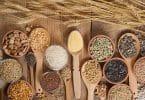 Cereais em colheres postas sobre mesa de madeira.