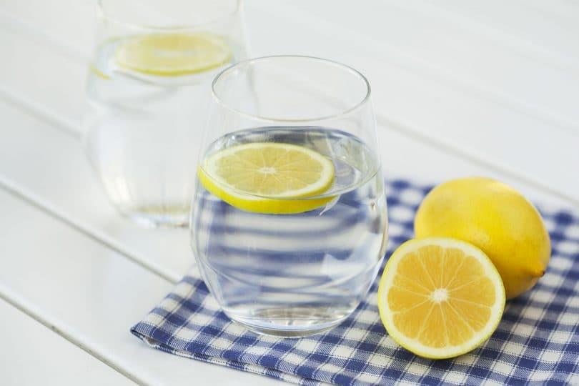 Dois copos com água e uma rodela de limão siciliano em cada. Um dos copos está sobre um pano xadrez. Ao lado, um limão siciliano inteiro, e metade de outro.