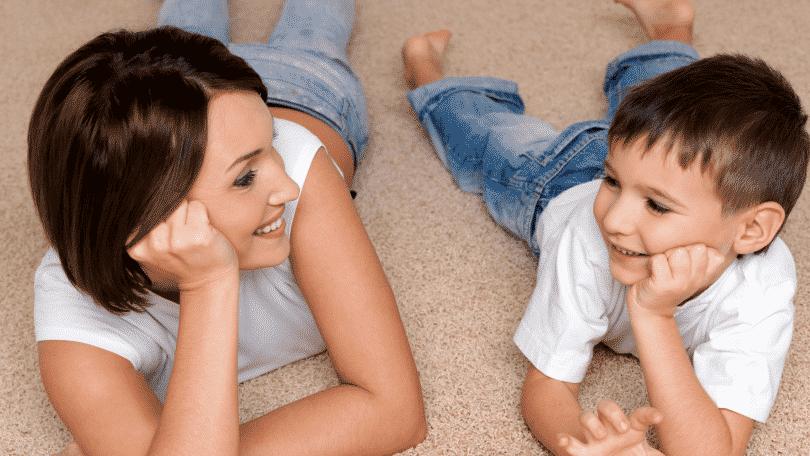 Mãe e filho se olhando, deitados no chão