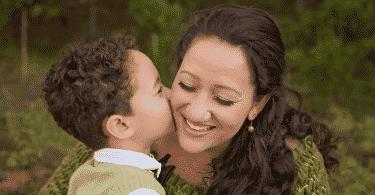 Menino beijando o rosto da mãe