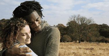 Casal de olhos fechados se abraçando na savana