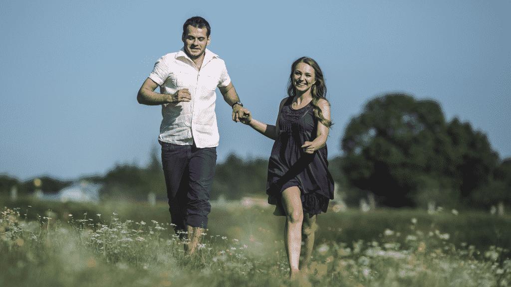 Casal feliz correndo no campo