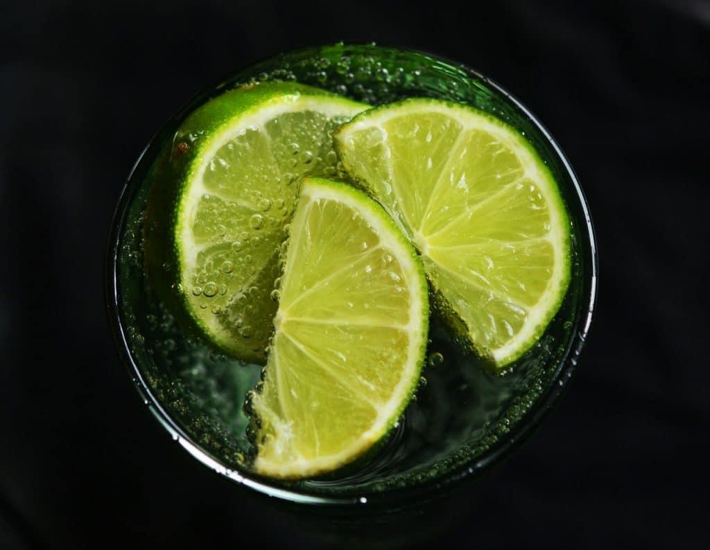pedaços de limão em um copo com água, vistos de cima.