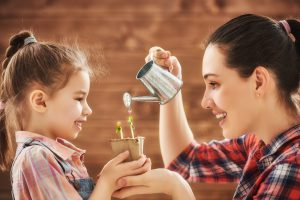 Cute child girl helps her mother to care for plants. Happy famil