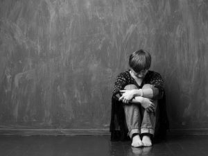 Domestic violence - hopeless victim is sitting on the floor hugging her knees. Black and white