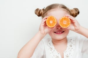 Little girl playing with fresh mandarin fruits