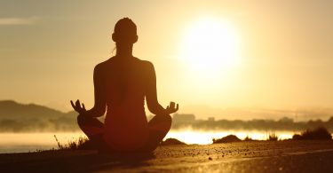 Silhouette of a fitness woman exercising yoga meditation exercises with the sun in the background