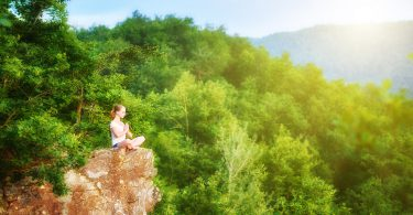 woman meditating in lotus posture doing yoga on top of the mountain on a rock in nature in the forest