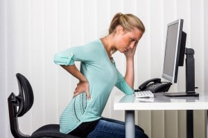 a woman sitting at a desk and has pain in the back. symbol photo