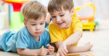 kids brothers read a book at home or nursery