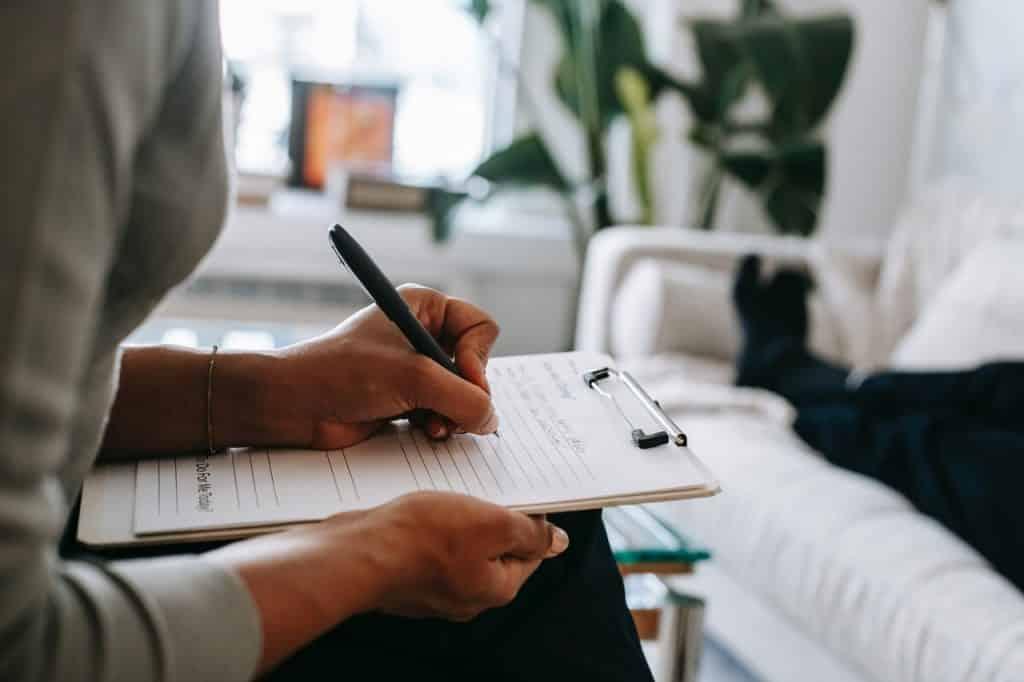 Recorte de uma mulher escrevendo em uma folha apoiada na prancheta.