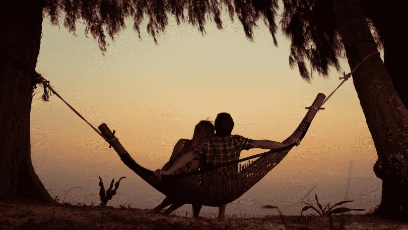 Silhueta de casal sentados juntos em uma rede