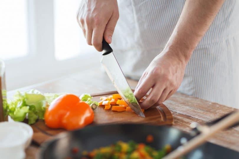 Mãos masculinas cortando pimentões em uma tábua de madeira.
